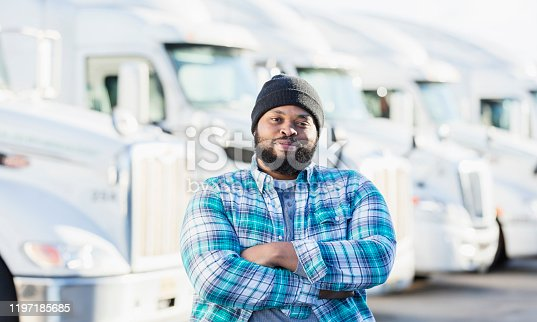 An African-American man in his 30s standing in front of a fleet of semi-trucks or tractor-trailers, arms crossed with a confident expression. He is an experienced truck driver or the owner of manager of a trucking company.