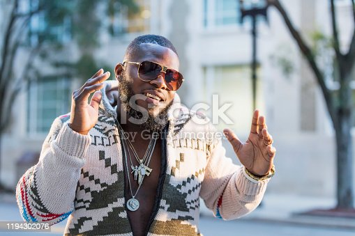 An African-American man with a gold grill and bling bling, waiting on a city street corner, smiling at the camera.