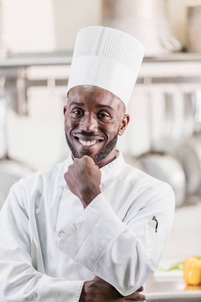 African-American man working as chef in restaurant A young African-American man in his 20s wearing chef's white, working in a commercial kitchen. He is smiling confidently at the camera, hand on his chin. chef's whites stock pictures, royalty-free photos & images