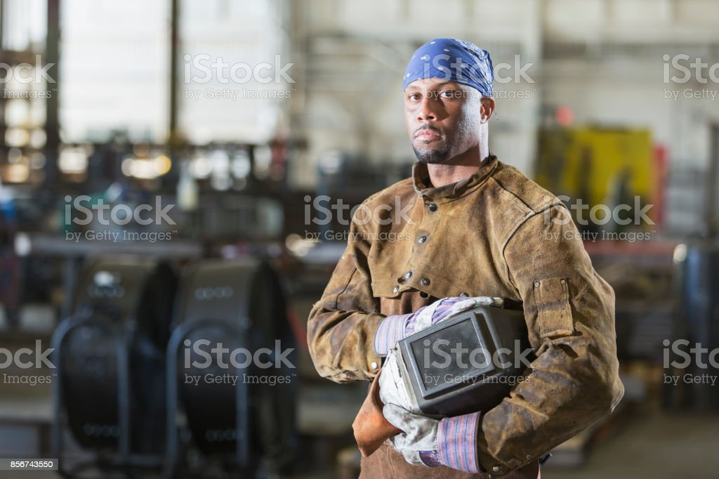 A mid adult African-American man working as a welder in a metal...