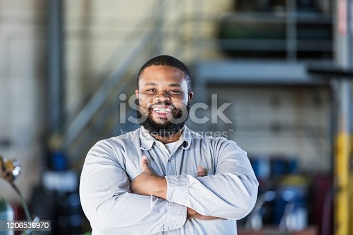A mid-adult African-American man in his 30s working in a repair shop. He is standing in the workshop looking at the camera, smiling, with his arms crossed.