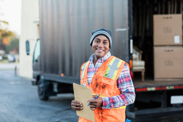 afrikanisch-amerikanischer mann, der arbeitet mit lieferwagen - umzug checkliste stock-fotos und bilder