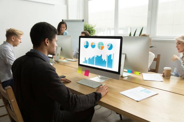 afrikanisch-amerikanischer manager arbeiten mit statistiken auf computer im vielvölkerstaat büro - projektmanager stock-fotos und bilder