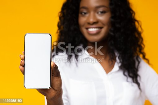 istock African-american millennial woman showing blank cellphone screen 1159988190