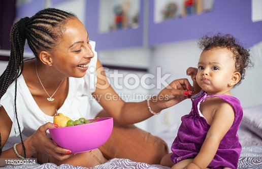 African-American Mother and Baby girl eating grapes