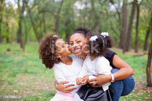 African-American mother and children hugging in the park