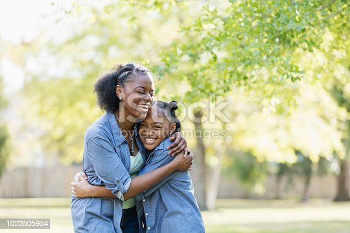1091098026istockphoto African-American mother and daughter outdoors, hugging 1023505954