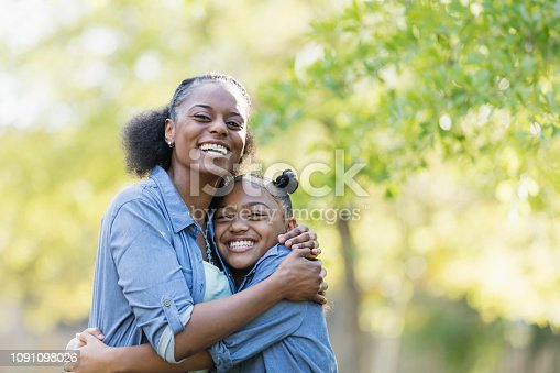 1091098026istockphoto African-American mother and daughter outdoors, hugging 1091098026