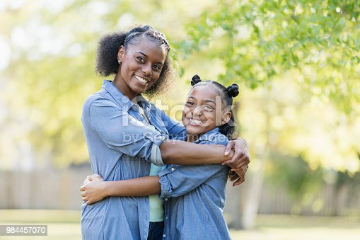 1091098026istockphoto African-American mother and daughter outdoors, hugging 984457070