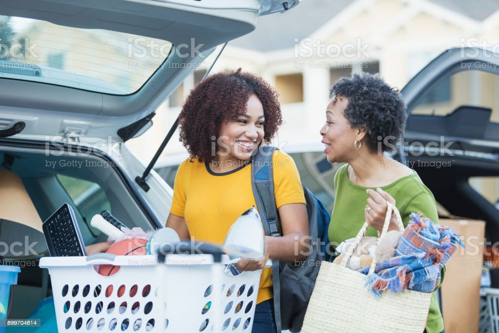 African-American mother helping daughter move stock photo