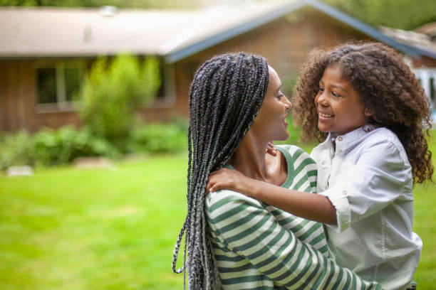 African-American mother holding son at house backyard stock photo
