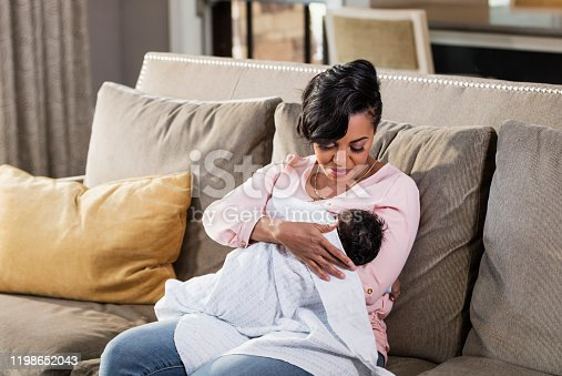A mid adult African-American woman in her 30s nursing her 2 month old baby boy, looking down at him, lovingly. The child is bundled in a blanket.