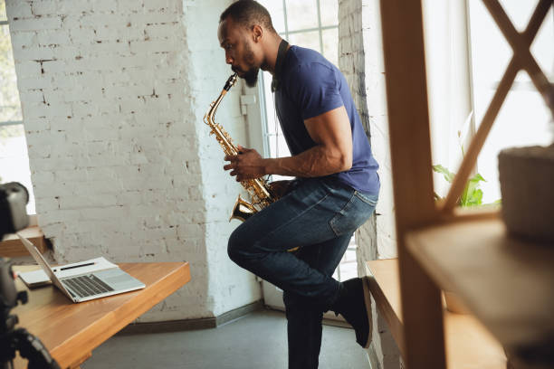 African-american musician playing saxophone during online concert at home isolated and quarantined, impressive improvising stock photo