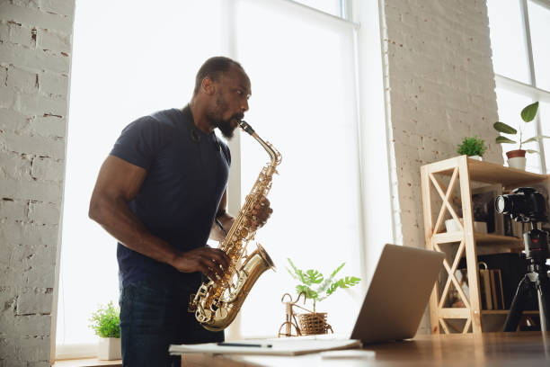 African-american musician playing saxophone during online concert at home isolated and quarantined stock photo