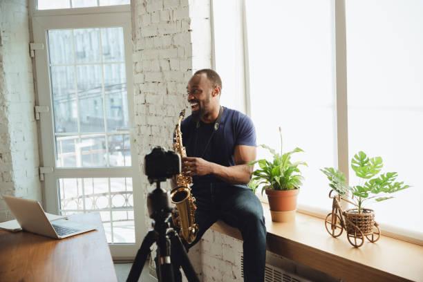 Afroamerikanischer Musiker spielt Saxophon während Online-Konzert zu Hause isoliert und unter Quarantäne, lachen – Foto
