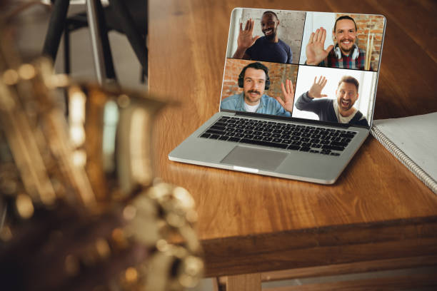 African-american musician playing saxophone during online concert or sound-check connected with the band at home quarantined, focus on laptop stock photo