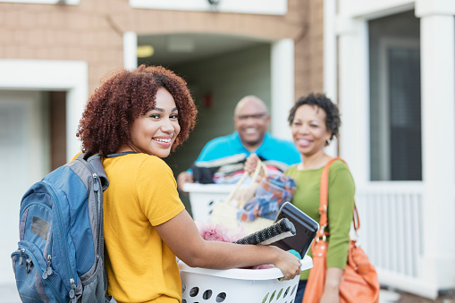 Mature African-American parents helping their daughter relocate, perhaps into an apartment or college dorm.  The young woman is in the foreground smiling at the camera, carrying a backpack and basket filled with her belongings.