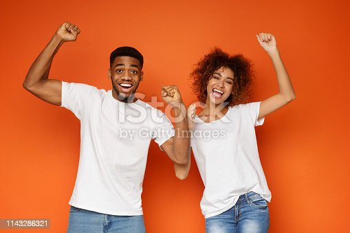 istock African-american partners rejoice success together on orange background 1143286321