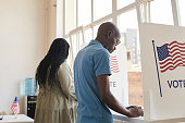 Back view portrait of young African-American people standing in voting booth and thinking, copy space