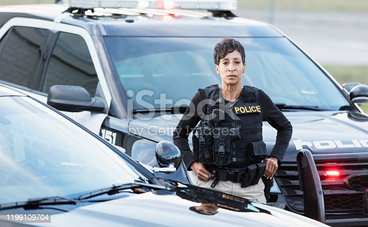 istock African-American policewoman standing by patrol car 1199109704