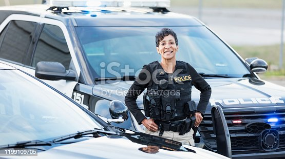 An African-American policewoman standing next to her patrol car, smiling confidently at the camera. She is a mature woman in her 40s, wearing a bulletproof vest and duty belt.