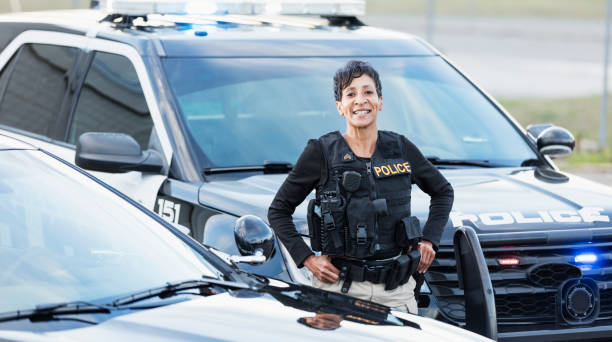 African-American policewoman standing by patrol car stock photo