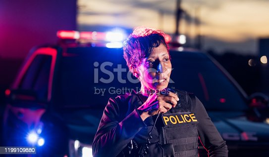 An African-American policewoman standing by her patrol car, talking on her radio with a serious expression on her face. She is a mature woman in her 40s, wearing a bulletproof vest and duty belt. It is nighttime and the emergency lights on her patrol car are flashing.