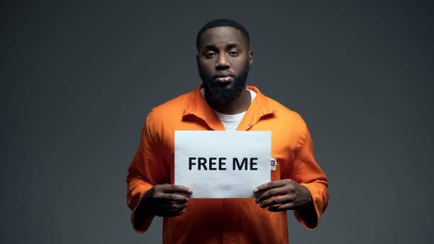 afro-amerikaanse gevangene houden gratis me inloggen cel, onschuldig vragen om hulp - onschuld stockfoto's en -beelden