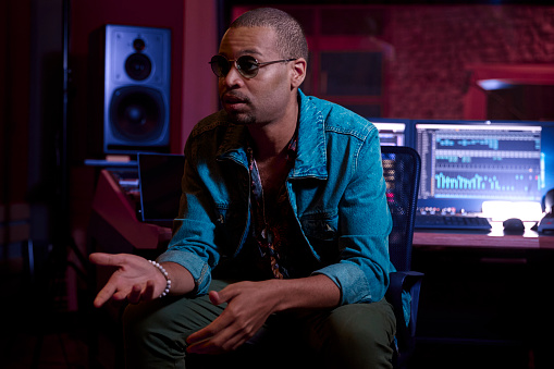 African-american male hipster producer speaking with artist about the music track in professional music studio