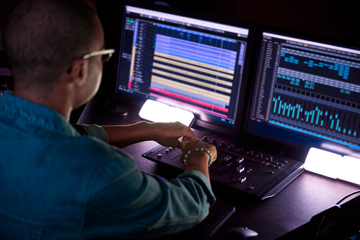 African-american man hipster producer working on music track on sound mixer control panel in professional music studio