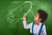 African-American schoolgirl with fishing rod in front of a blackboard