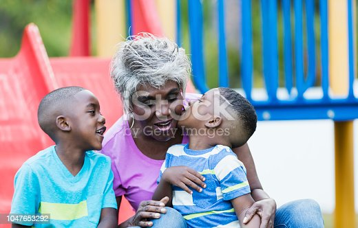 An African-American senior woman in her 60s sitting between her two grandsons on a slide on the playground. The brothers are 4 and 5 years old, giving their grandmother a kiss.