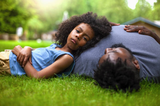 African-American son and father lie down on grass at backyard stock photo