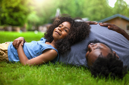 African-American son and father rests on grass at backyard holiday villa