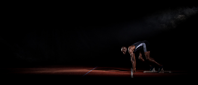 Side view of an African-American sprinter on the starting line about to start running. Black background.