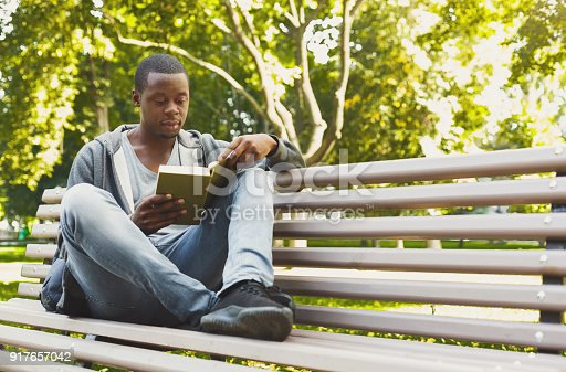 istock African-american student reading a book outdoors 917657042
