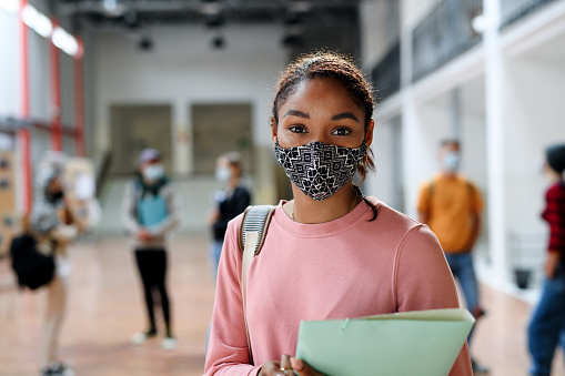 Portrait of african-american student with face mask back at college or university, coronavirus concept.