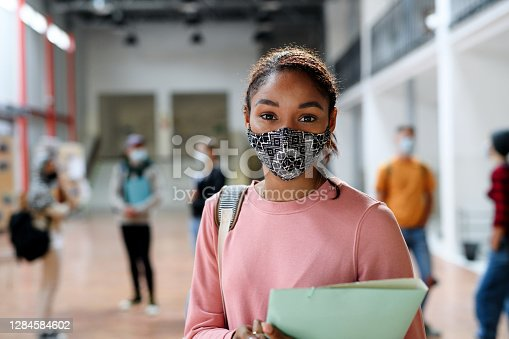 istock African-american student with face mask back at college or university, coronavirus concept. 1284584602