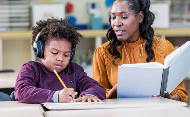 African-American teacher and elementary school student stock photo