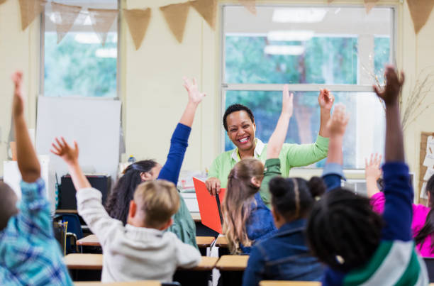 African-American teacher reading to school children stock photo