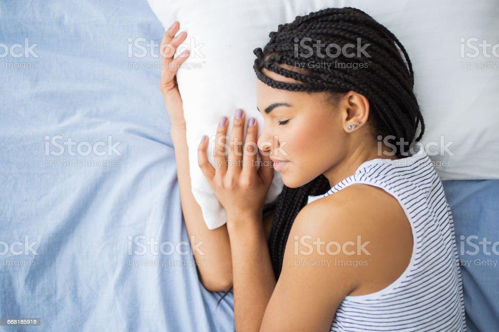 African-American teenage girl sleeping in bed stock photo