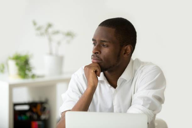 african-american nachdenklich geschäftsmann hält hand am kinn, die planung von zukünftigen projekten - männer zitate stock-fotos und bilder