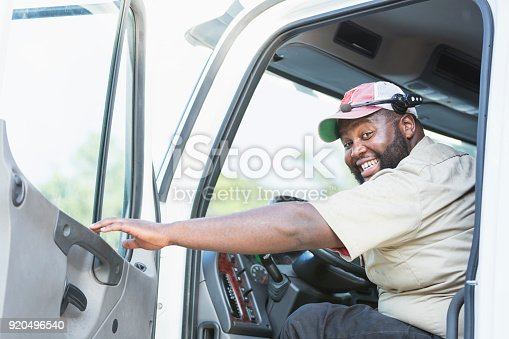A truck driver looking at the camera as he sits in the driver's seat, reaching to close the vehicle door. He is an African-American man in his 30s with a large build and a smile on his face.