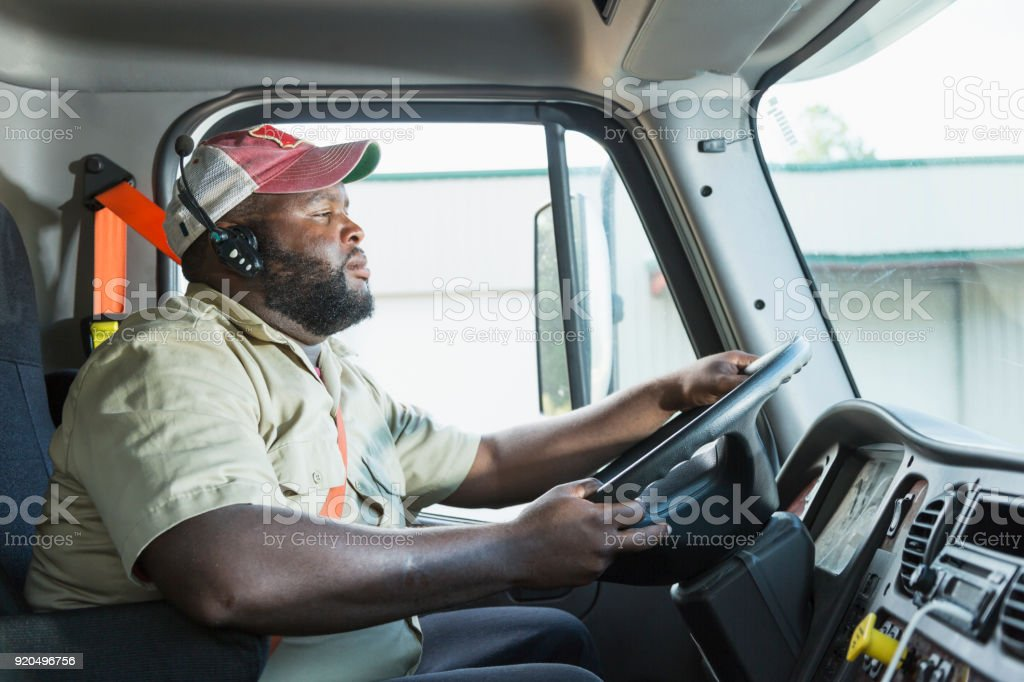 African-American truck driver in driver's seat stock photo