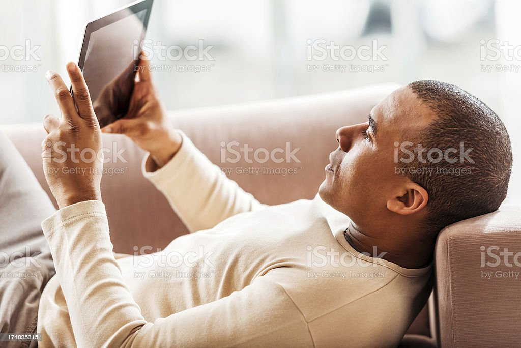 African-American using digital tablet at home. royalty-free stock photo