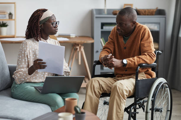 African-American Wheelchair User Talking to Business Consultant stock photo