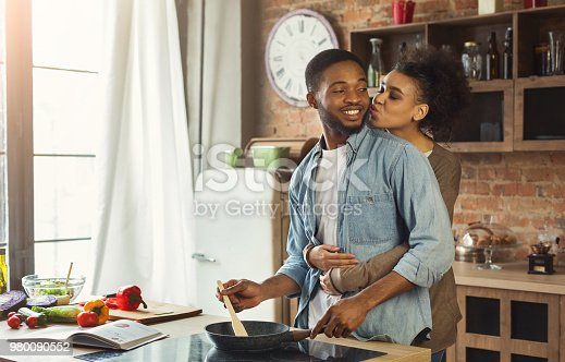istock African-american wife kissing husband in kitchen 980090552