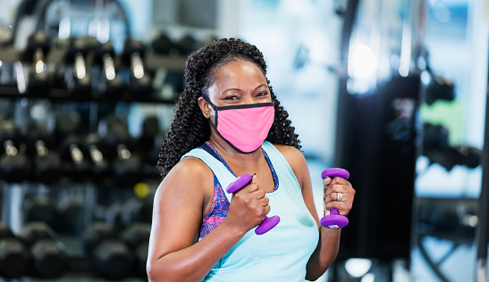 A mature African-American woman in her 40s working out at the gym, lifting hand weights. She is exercising during the covid-19 pandemic, wearing a protective face mask to prevent the spread of coronavirus.