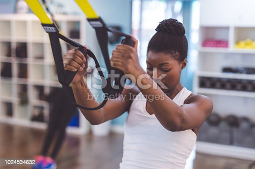istock African-American woman does a suspension workout at the gym 1024534632