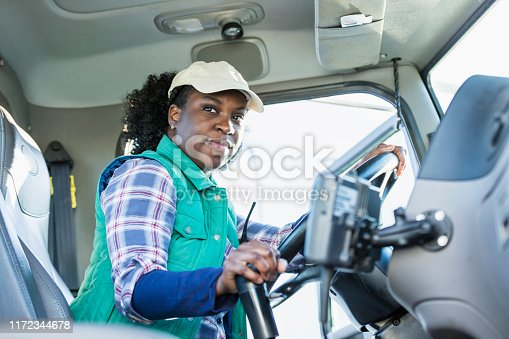 An African-American woman in her 30s sitting in the driver's seat of a semi-truck, looking at the camera.